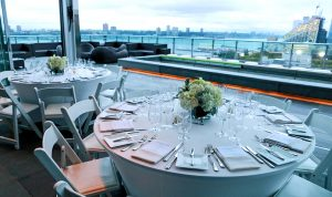 Tables all set over looking Hudson River Press lounge NYC